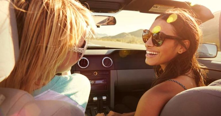 two smiling girls in a convertible car