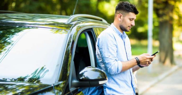 Man leaning against his car and looking at his phone