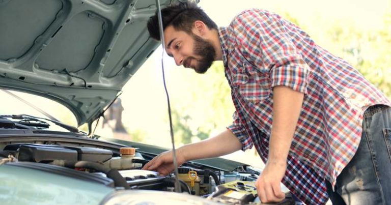 Man looking under the hood of his car