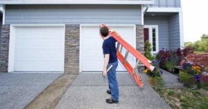 Man holding ladder and hammer in front of two car garage