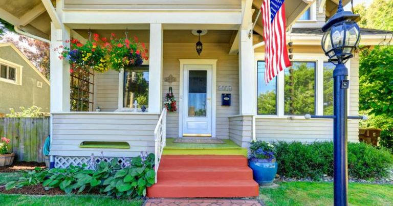 Pretty front porch with flower baskets and American flag
